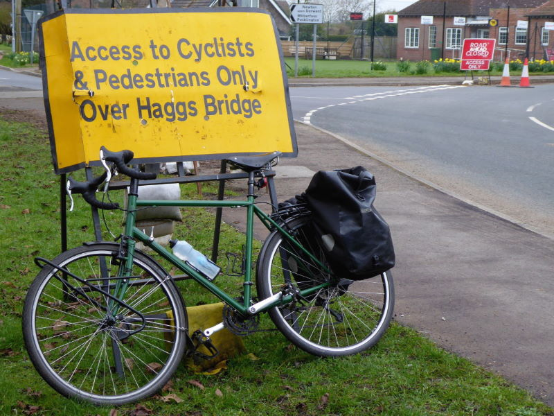 Sign at road closure for Hagg Bridge, SE of York, stressing that cyclists CAN continue and use the bridge